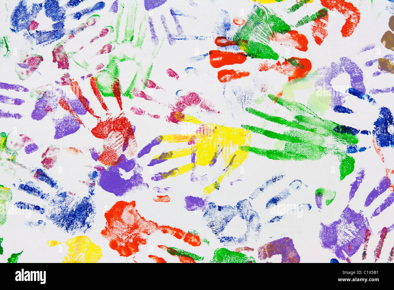 Varicoloured imprint of the hands on white canvas - Stock Image