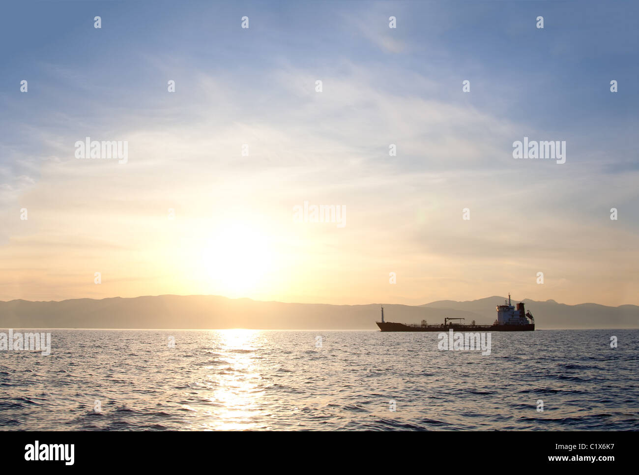 Bulk-carrier ship at sunset in the sea - Stock Image