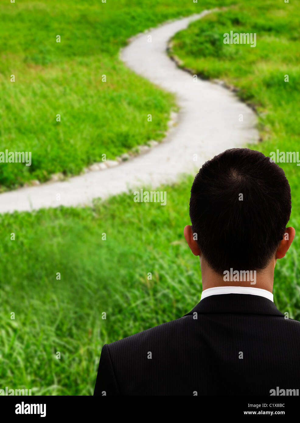 Business man thinking and watching the curved road - Stock Image