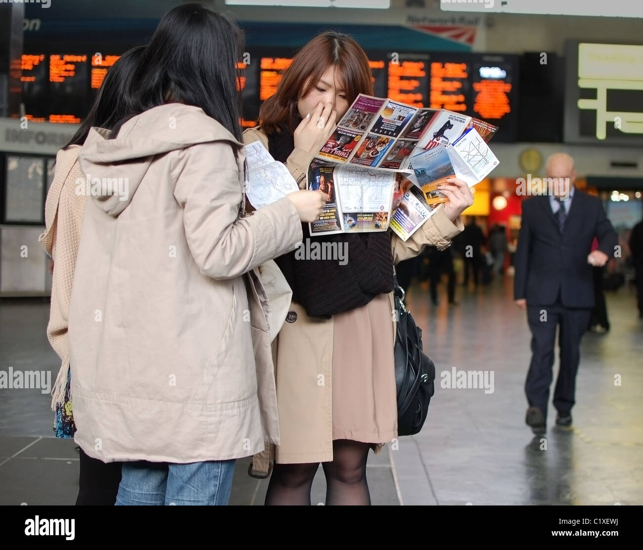 Tourists browsing a map in London Euston station - Stock Image