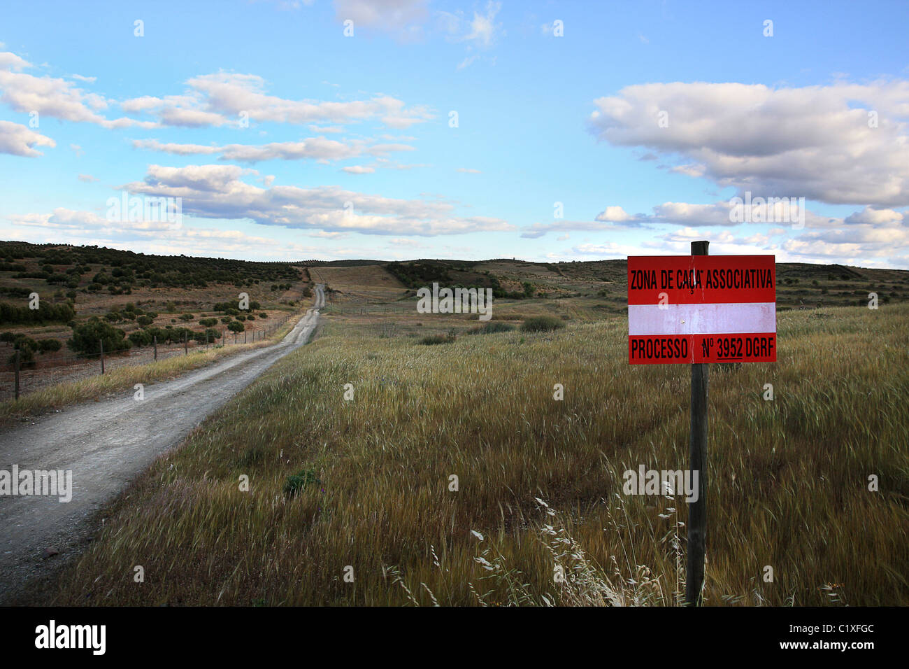 View of a dirt road on the countryside region with a hunting ground sign on Algarve/Portugal. - Stock Image