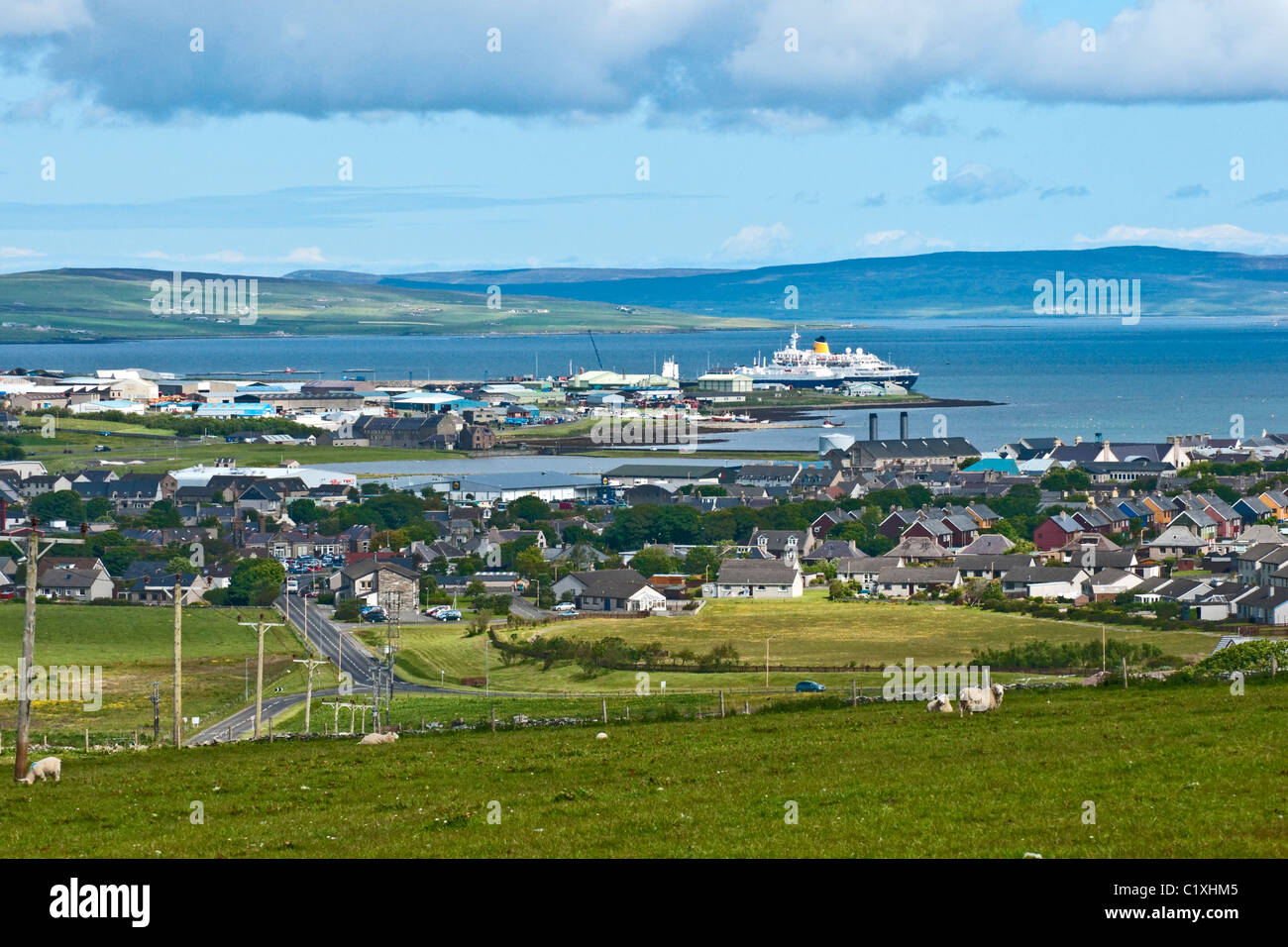 A general view over Kirkwall in Orkney towards the harbour with cruise ship at the pier - Stock Image