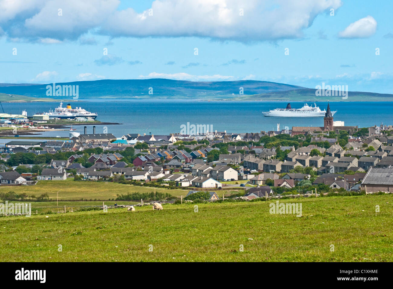 A general view over Kirkwall in Orkney towards the harbour with cruise ships at the pier and anchored in Kirkwall - Stock Image