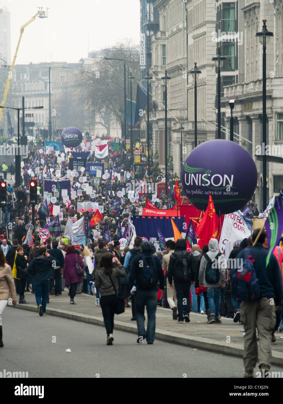 Protesters march down Piccadilly in London during the TUC organised protest against public spending cuts on 26 March - Stock Image