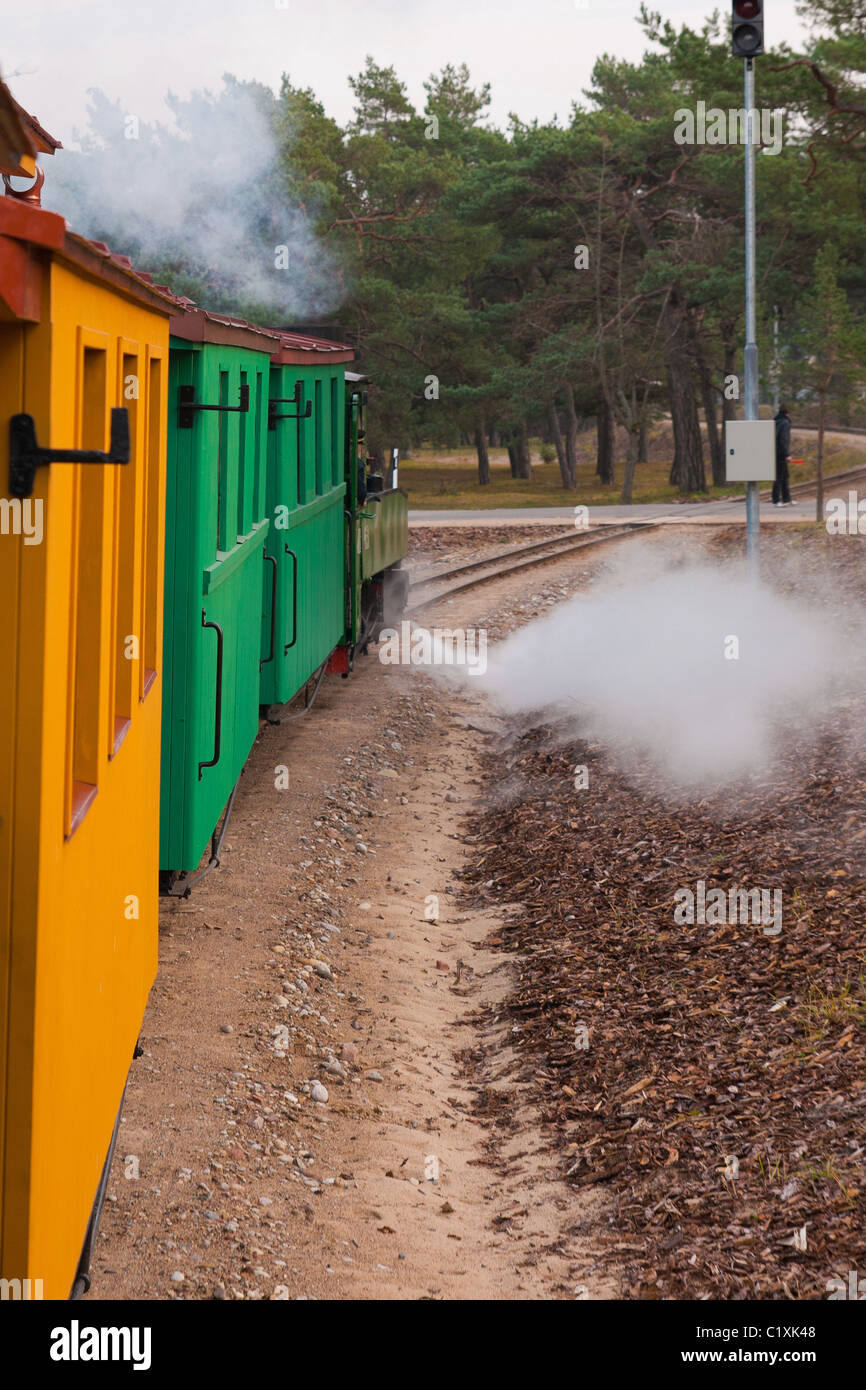 An old steam train pulls colorful waggons - Stock Image