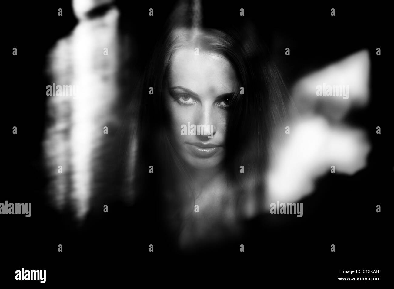 Female witch behind the dark glass with reflections - Stock Image