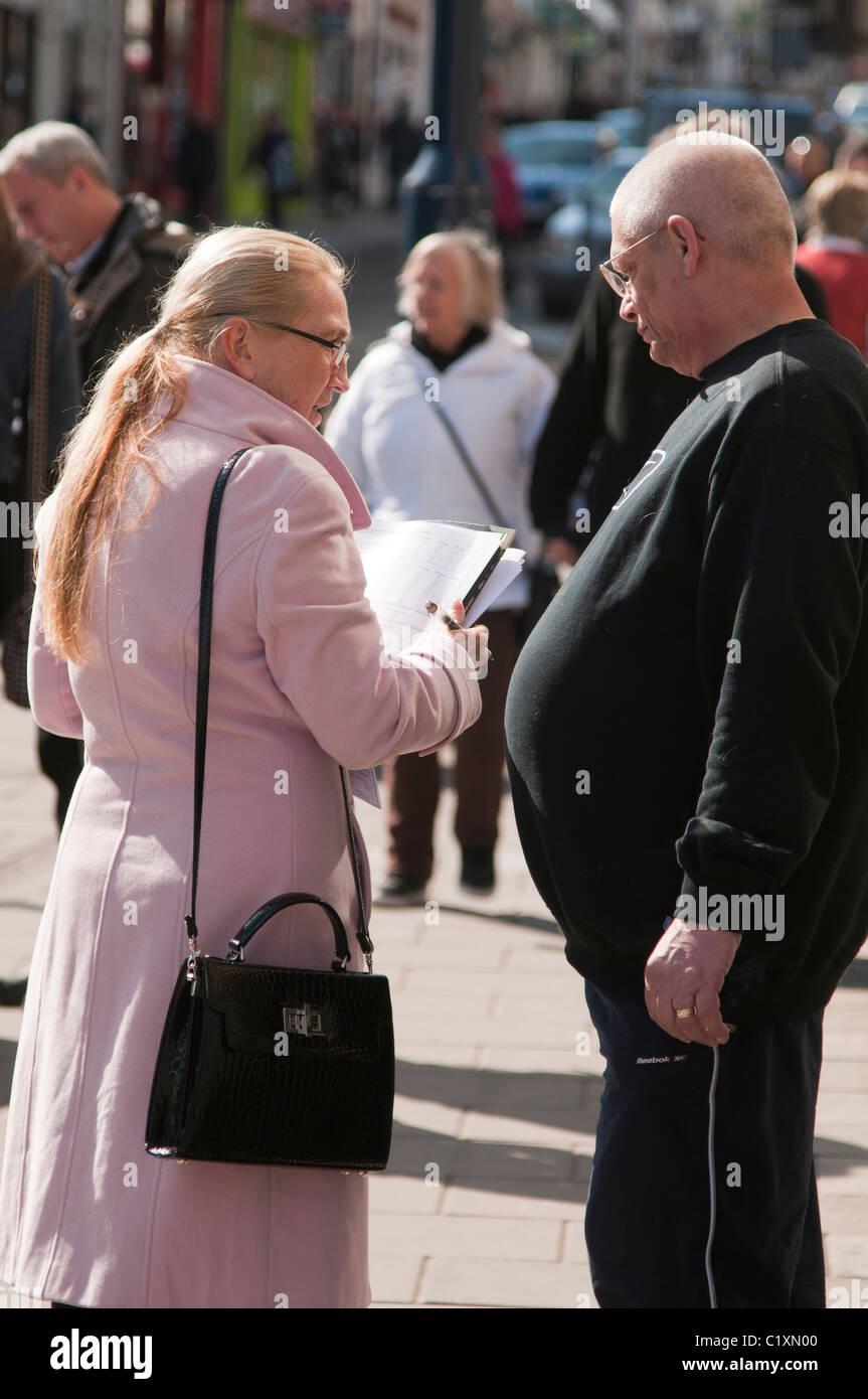 A woman pollster interviewer doing a street questionnaire public opinion poll survey, UK Stock Photo
