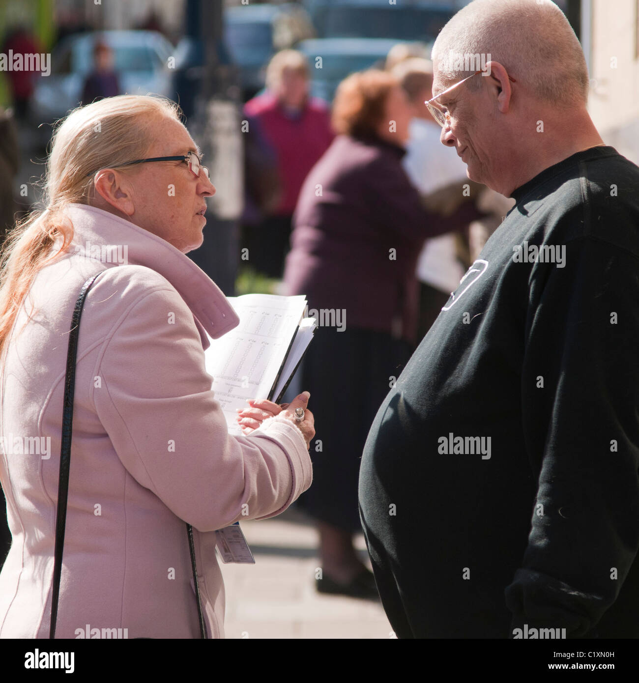 A woman doing a street questionaire public opinion poll survey, UK - Stock Image