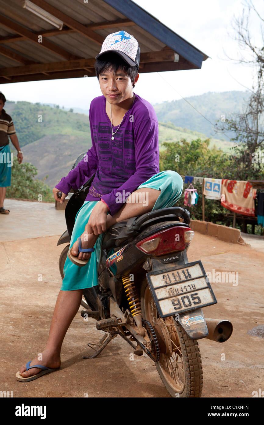 Young Lisu boy siting on the motorbike, Ban Hai Ko, Mae Salong, Chiang Rai, Thailand - Stock Image