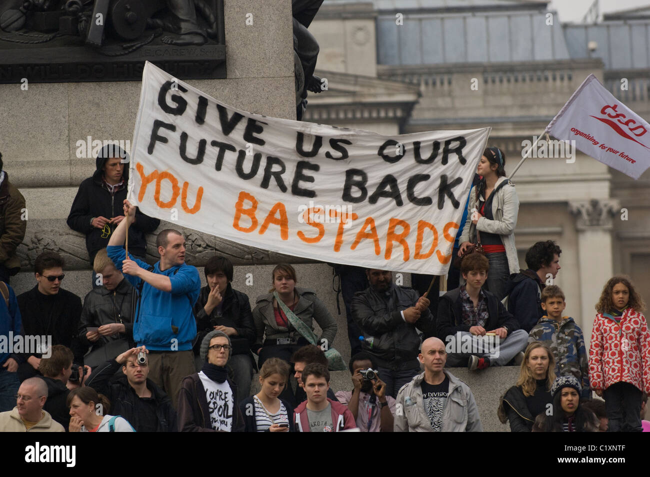 Protesters against UK government cuts with banner at the base of Nelson's Column in London's Trafalgar Square, - Stock Image