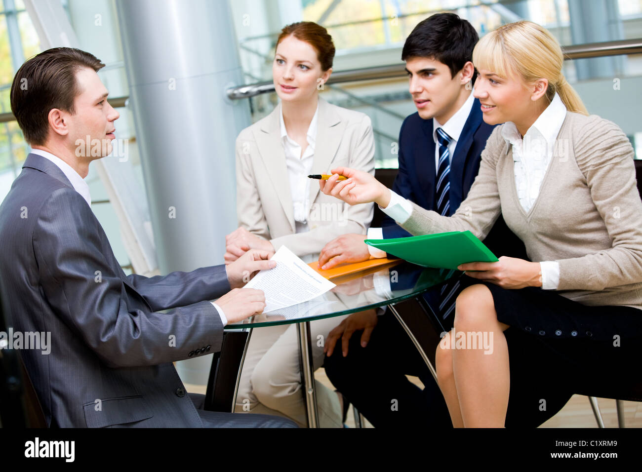 Friendly group of specialists speaking to businessman during negotiations Stock Photo