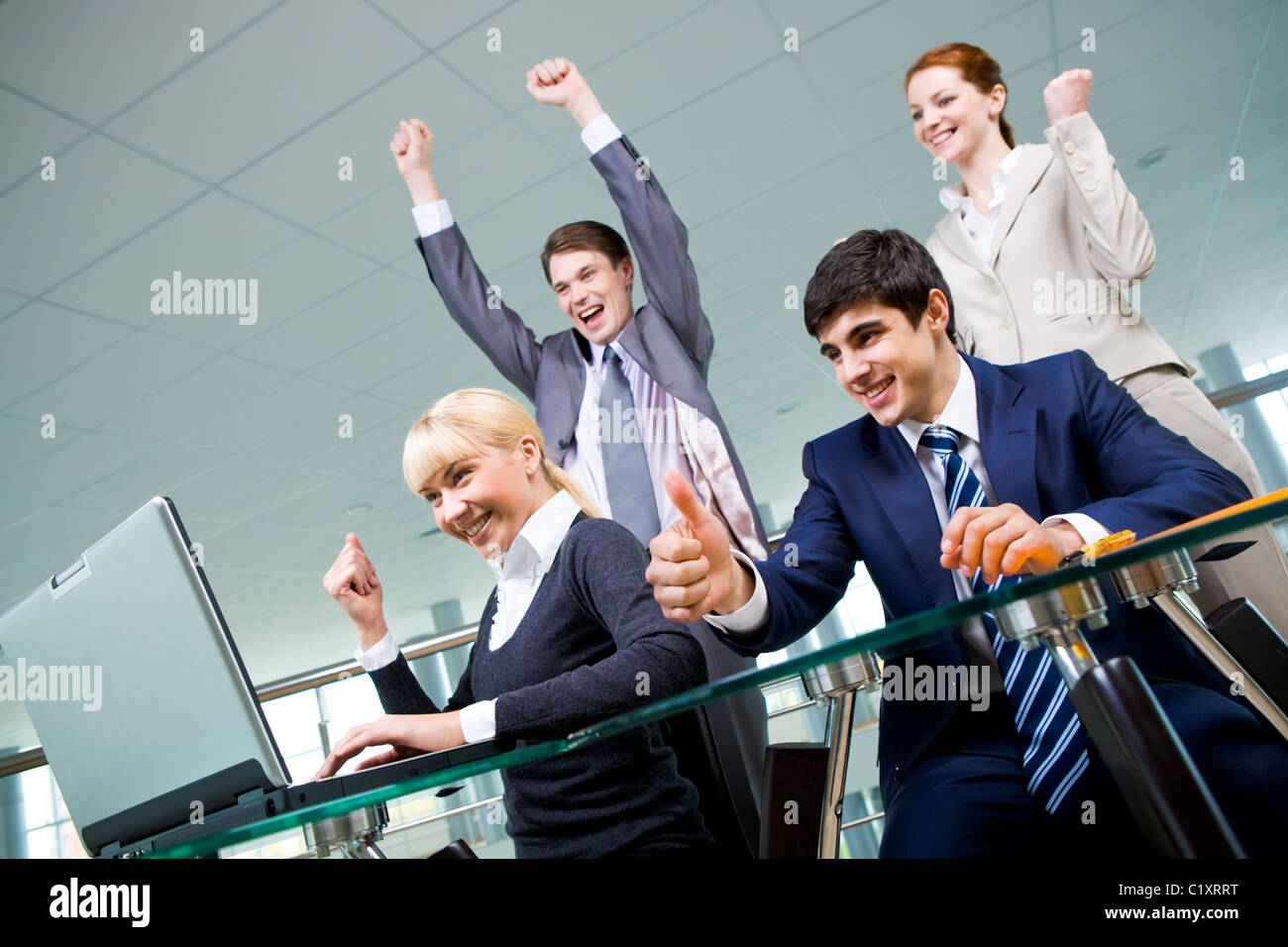 Group of co-workers looking at laptop monitor with expression of gladness - Stock Image