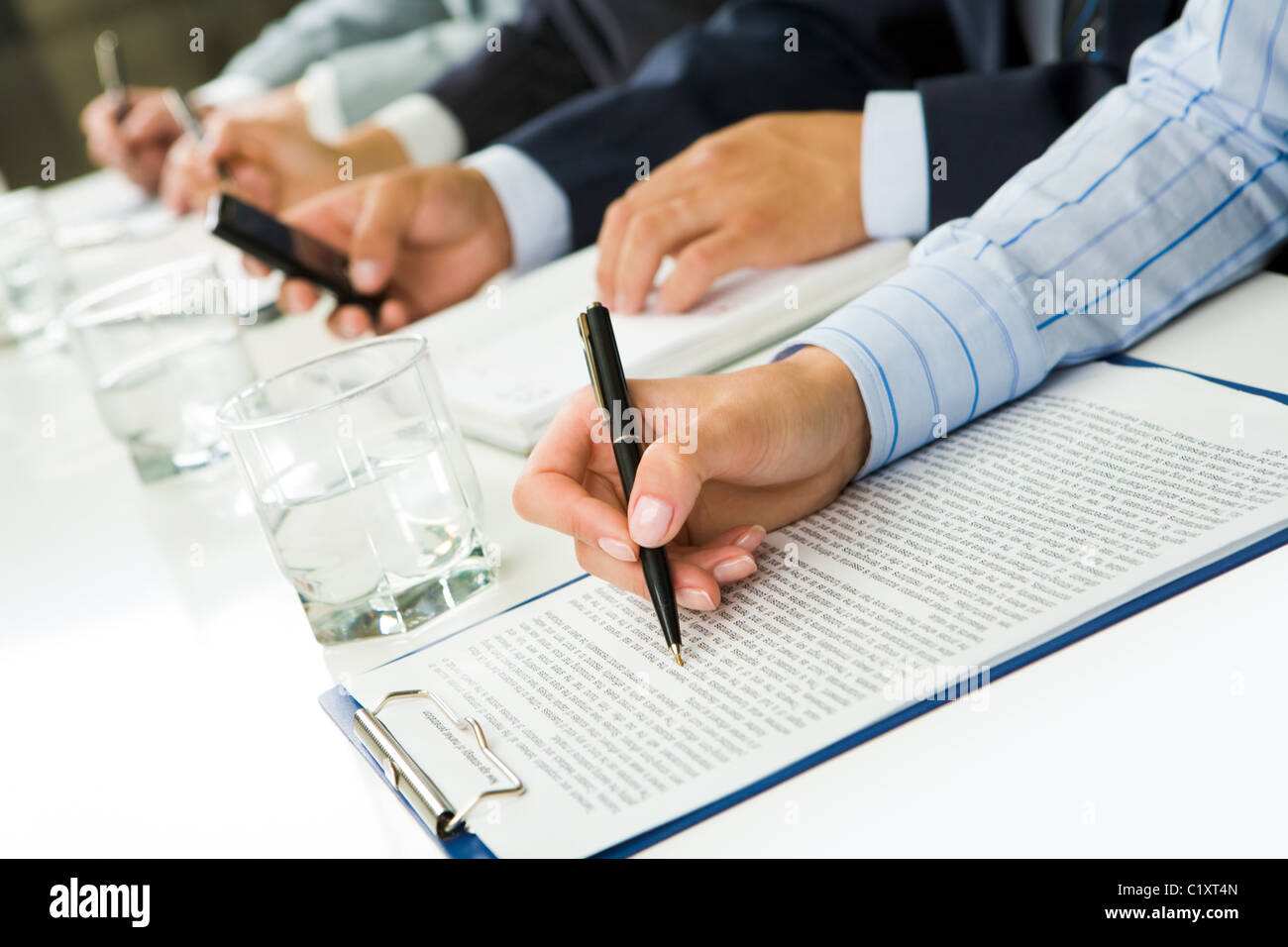 Image of human hand over paper during business seminar - Stock Image