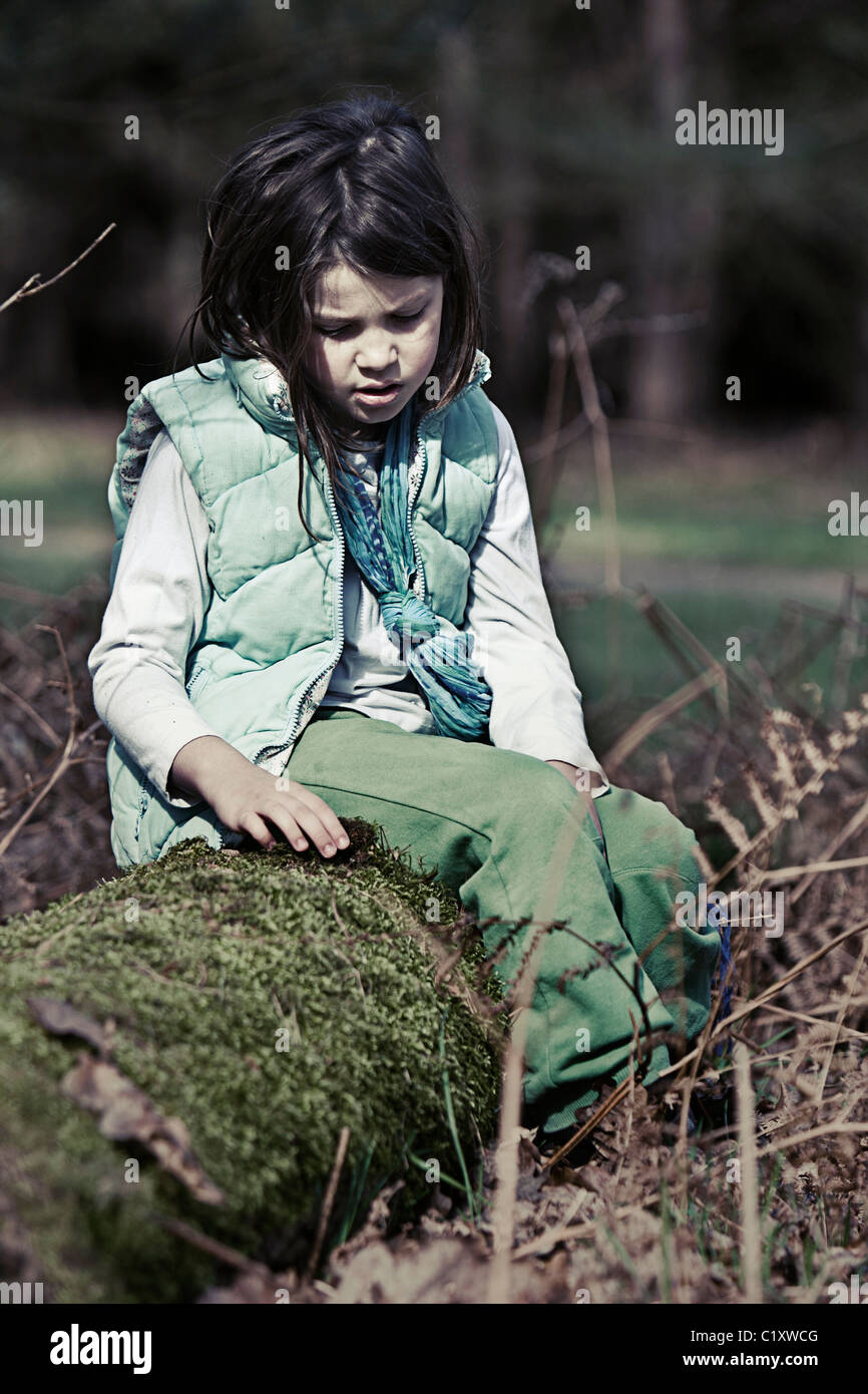 Child Sitting on Log in Forest - Stock Image
