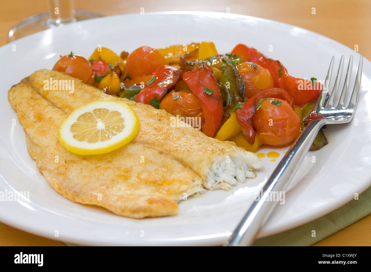 Lightly dusted plaice fillet with roasted salad. - Stock Image
