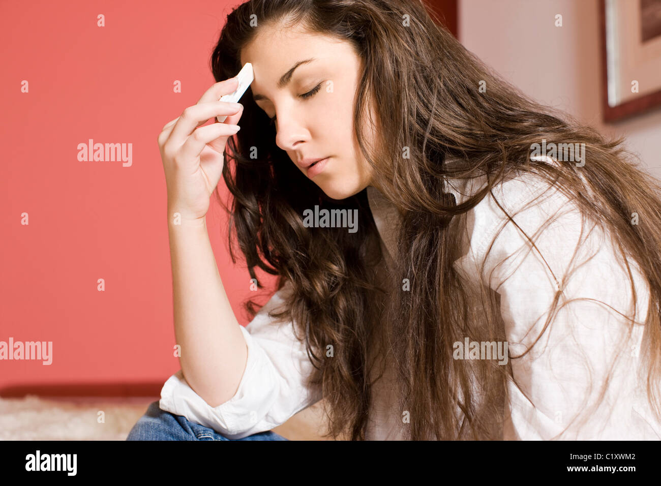 Worried woman holding pregnant test - Stock Image