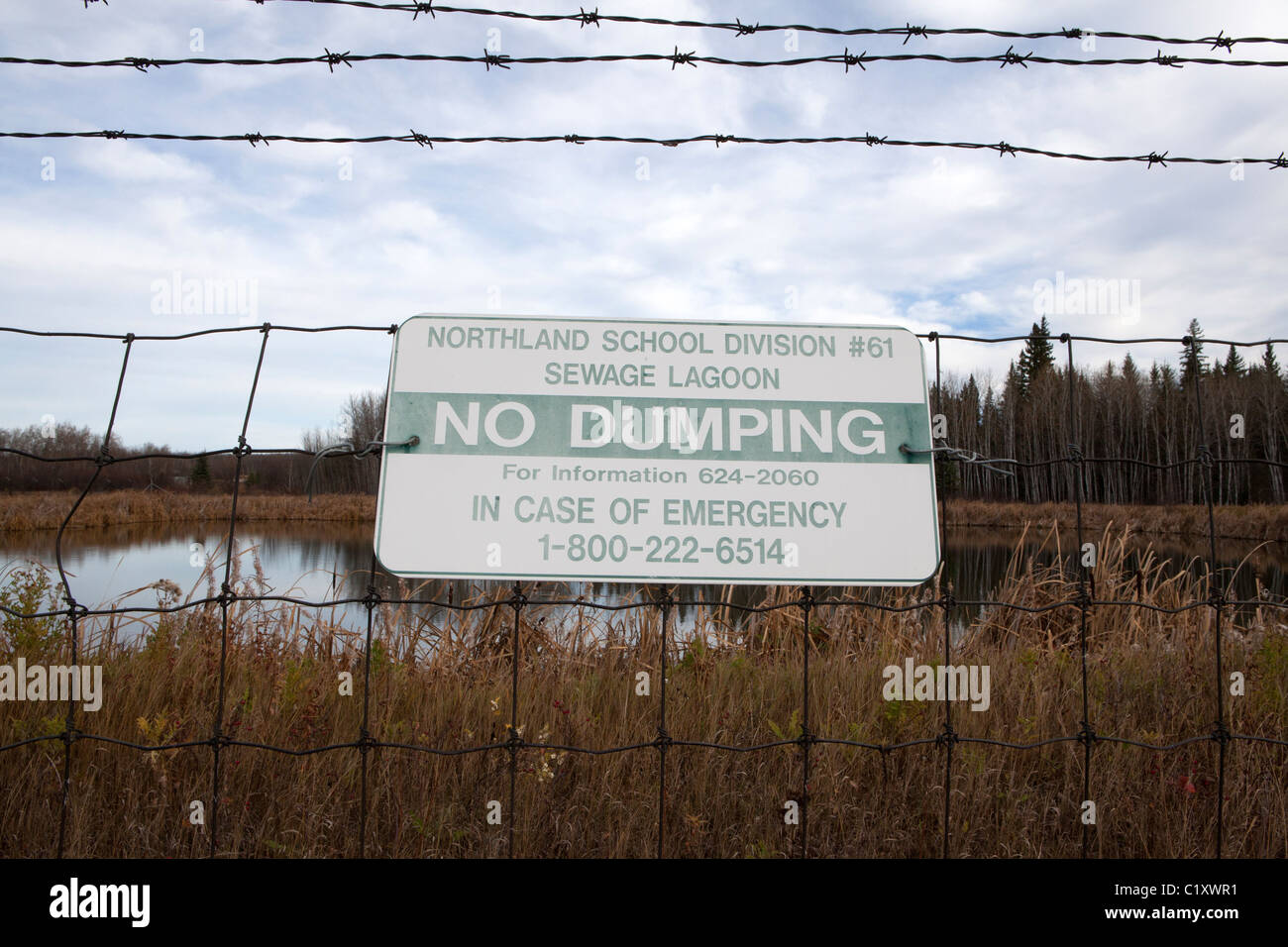 Warning sign on wire fence in front of sewage lagoon, Peace River, Alberta, Canada - Stock Image