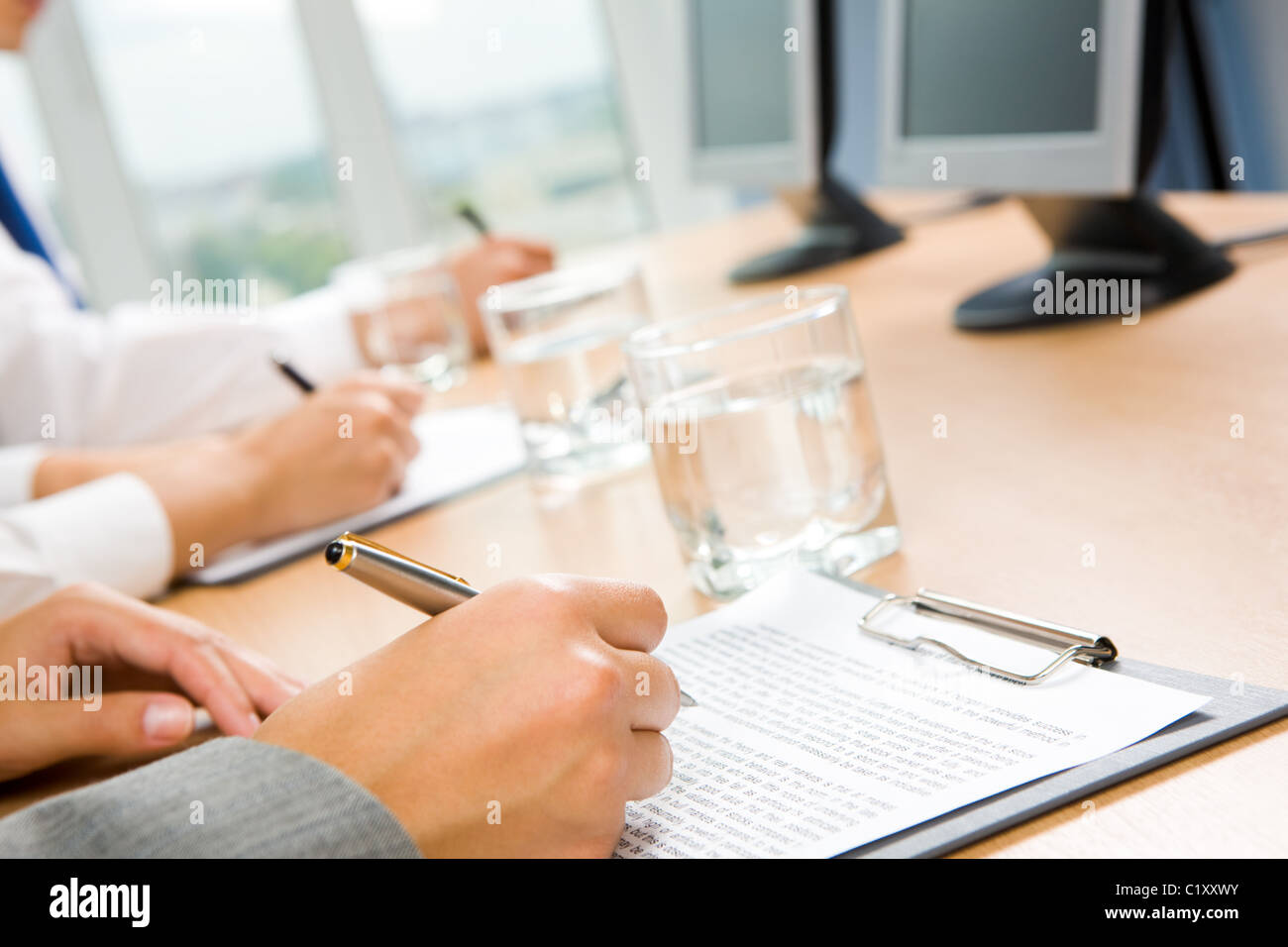 Image of human hand holding pen and making notes with glass of water and monitors near by - Stock Image