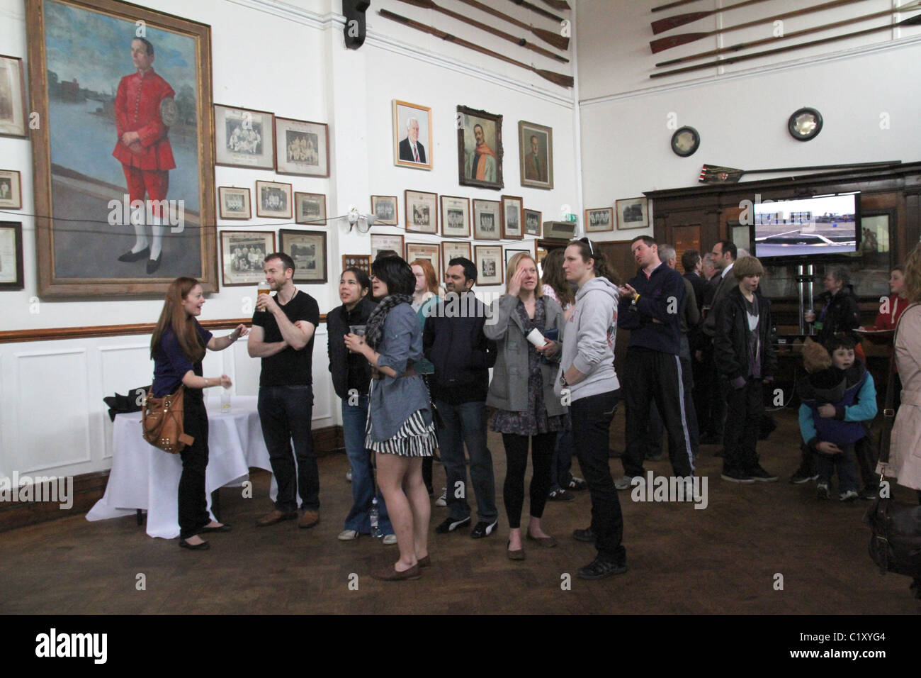 UK. SPECTATORS AT  OXFORD VS. CAMBRIDGE BOAT RACE AT WIMBLEDON ROWING CLUB BY THAMES RIVER - Stock Image