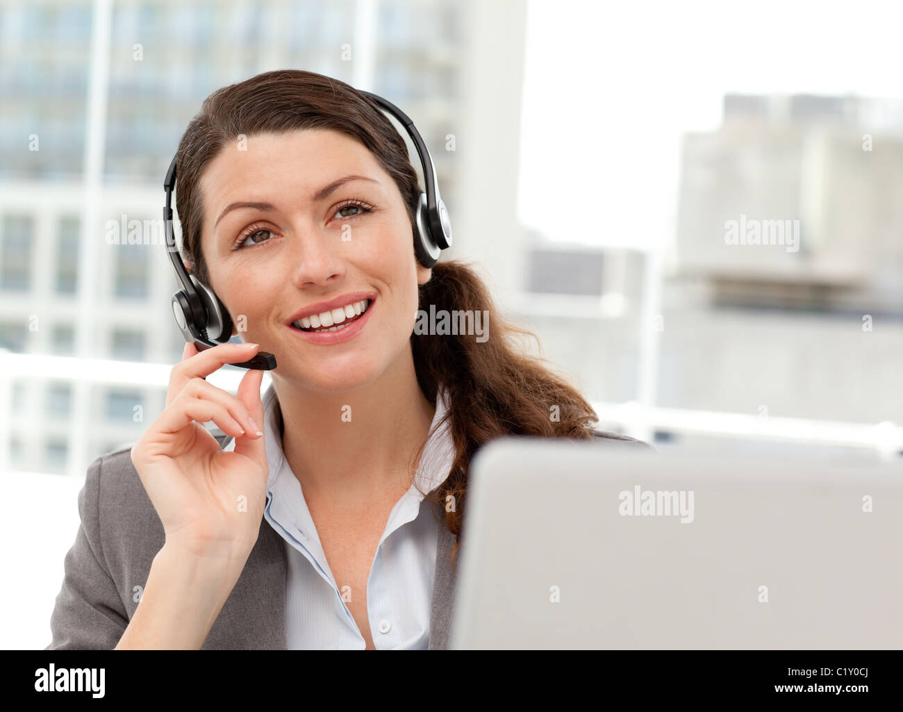 Thoughtful businesswoman talking on the phone while working on her computer Stock Photo
