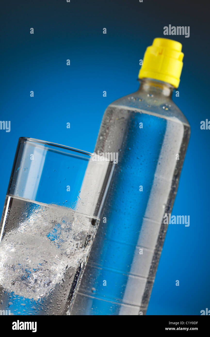 mineral water bottle and glass filled with ice cubes, tilted view - Stock Image