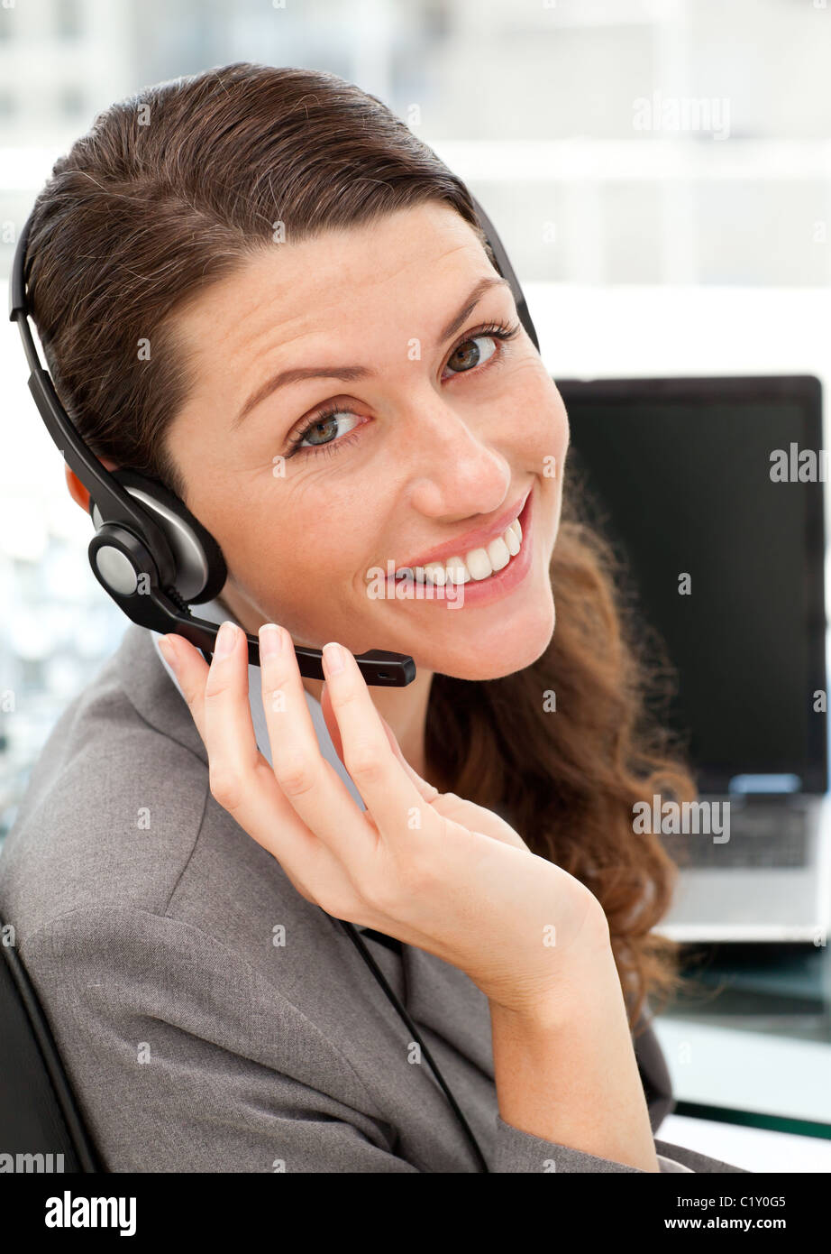 Pretty female representative on the phone with earpiece on Stock Photo