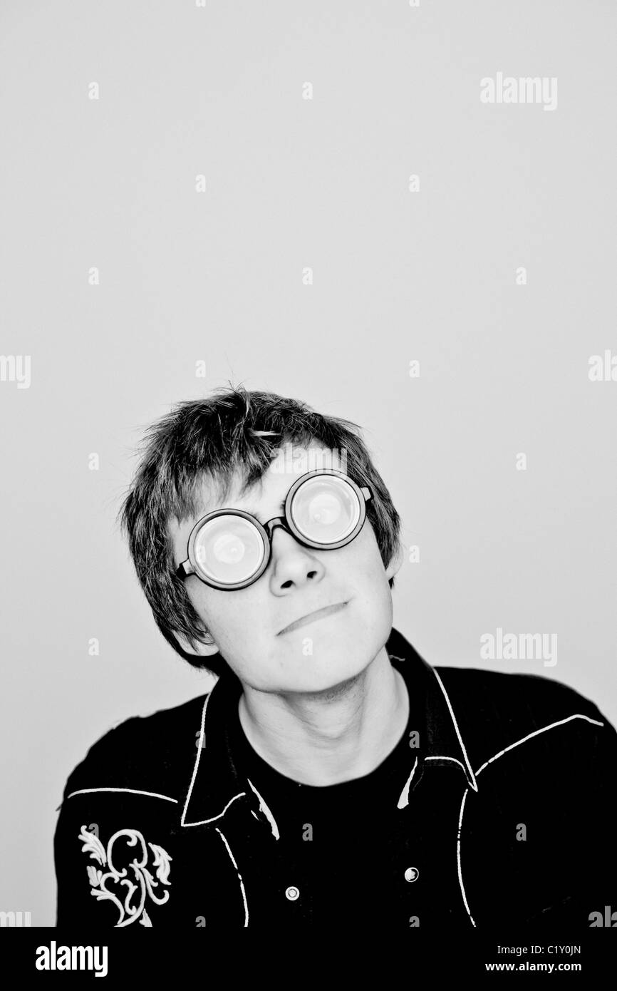 A teenage boy wearing round opaque glasses - Stock Image