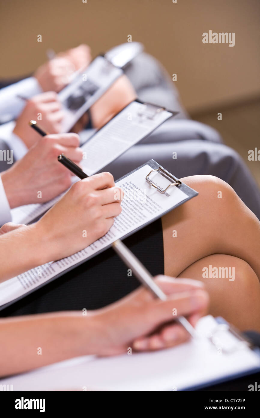 Row of business people writing lecture at seminar - Stock Image