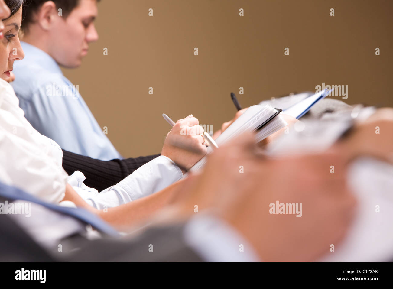 Close-up of female making notes or writing business plan at conference - Stock Image