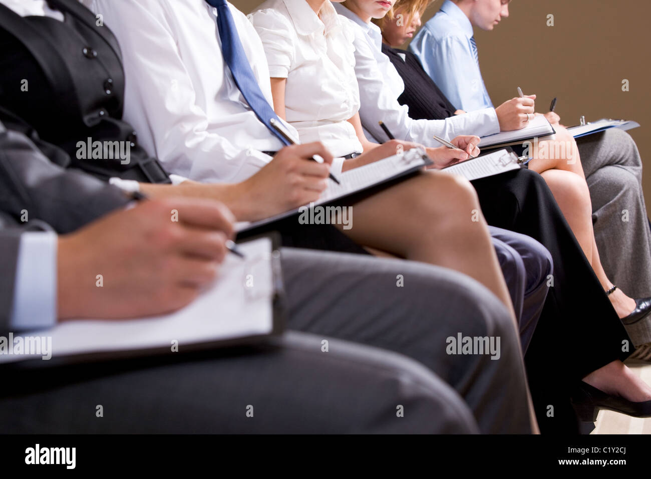 Close-up of business people making notes or writing business plan at conference - Stock Image