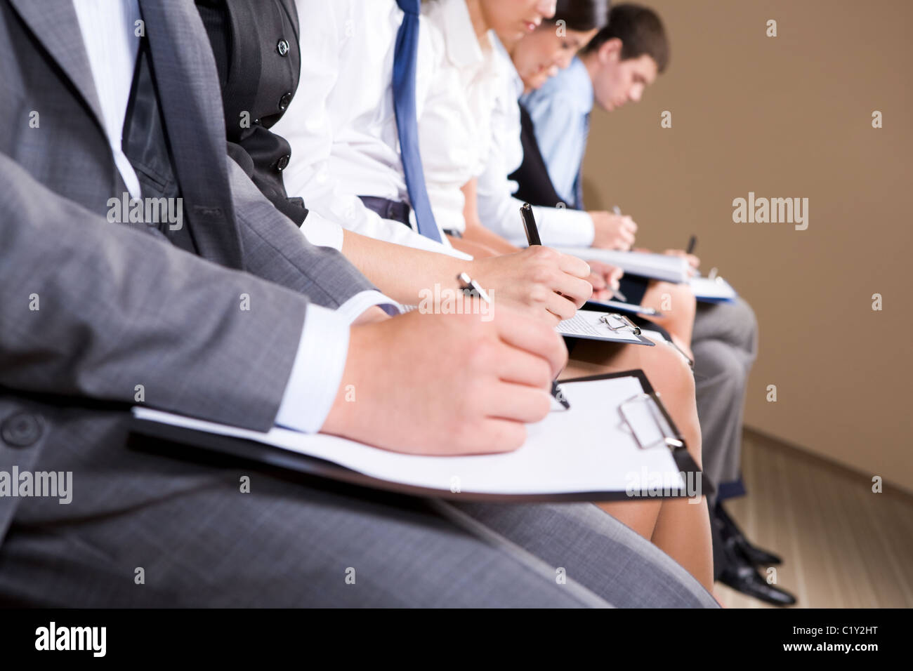 Row of business people making notes or writing business plan - Stock Image