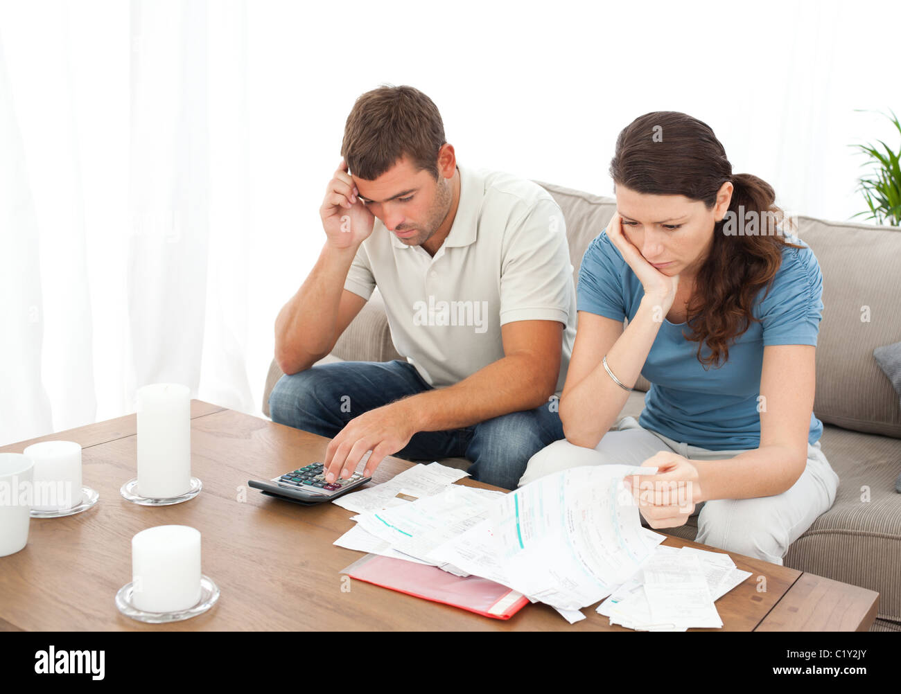 Desperate couple doing their accounts sitting on the sofa - Stock Image