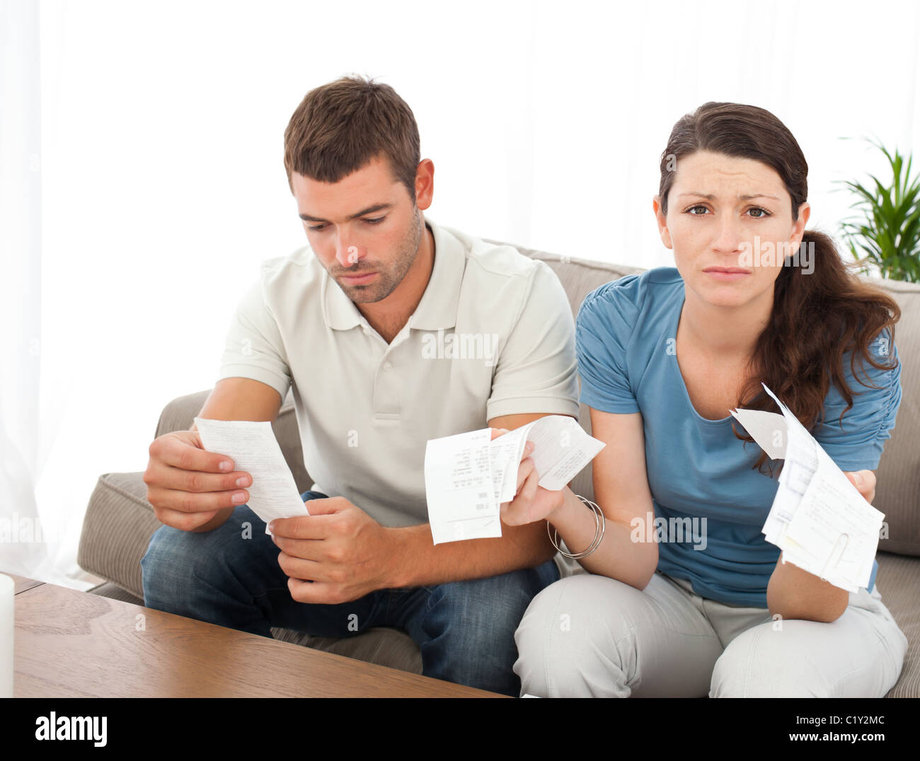 Desperate woman doing her accounts with her boyfriend sitting on the sofa - Stock Image