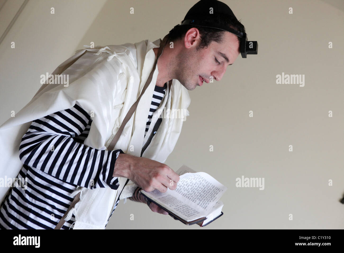 Young Jewish man with tallith and Tefillin - Stock Image