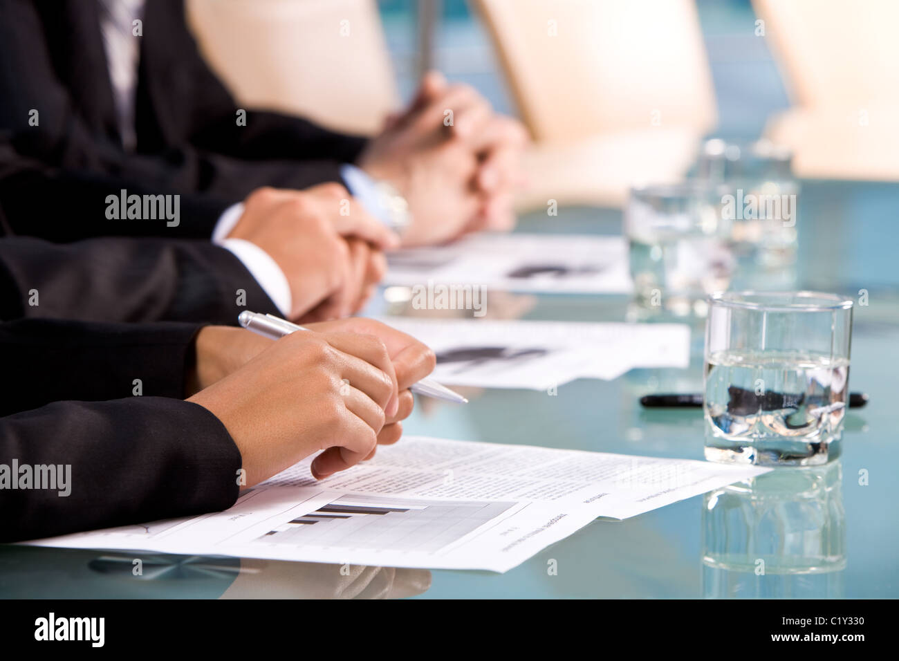 Row of human hands on workplaces with papers during conference - Stock Image