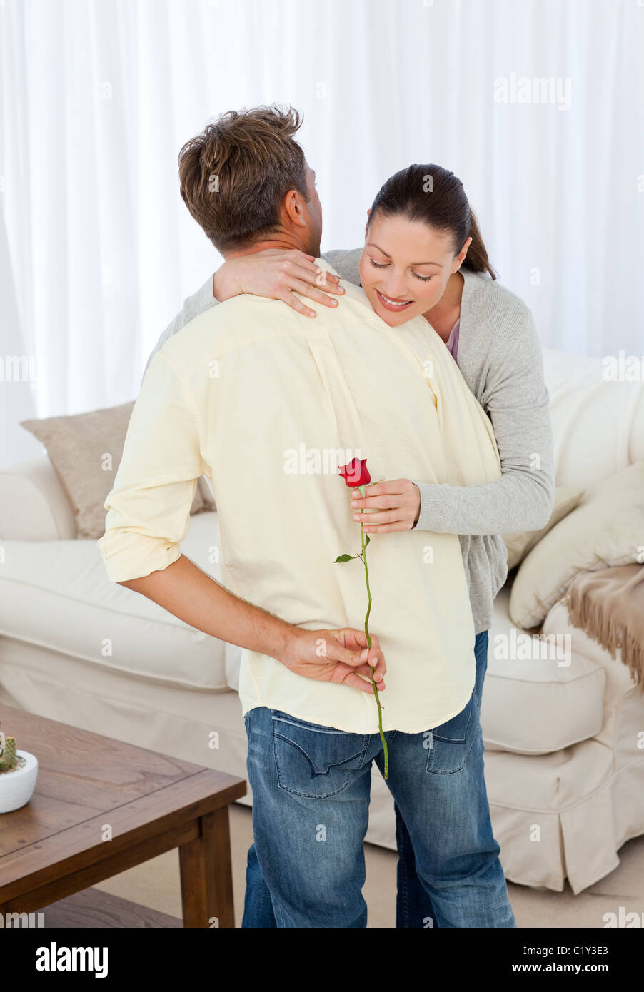 Hasty woman looking at rose hidden behind her boyfriend - Stock Image