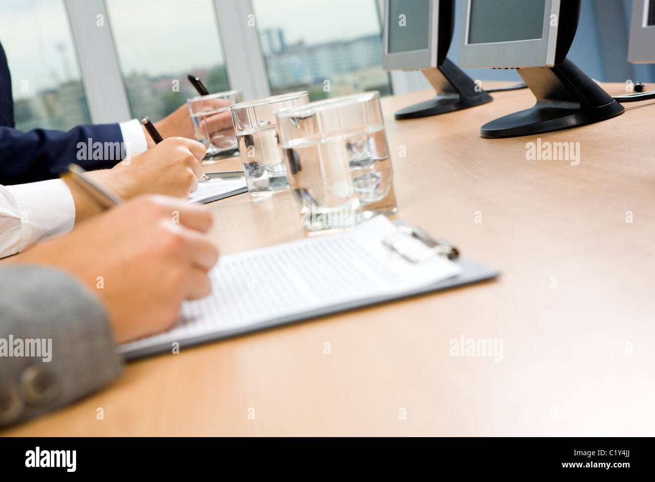 Row of human hands holding pen and making notes with glass of water and monitors near by - Stock Image