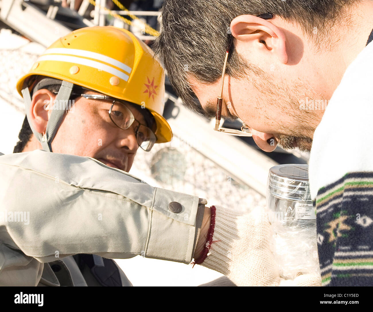 A member of the so-called Fukushima 50 is given a radiation check prior to boarding the Kaiwomaru - Stock Image