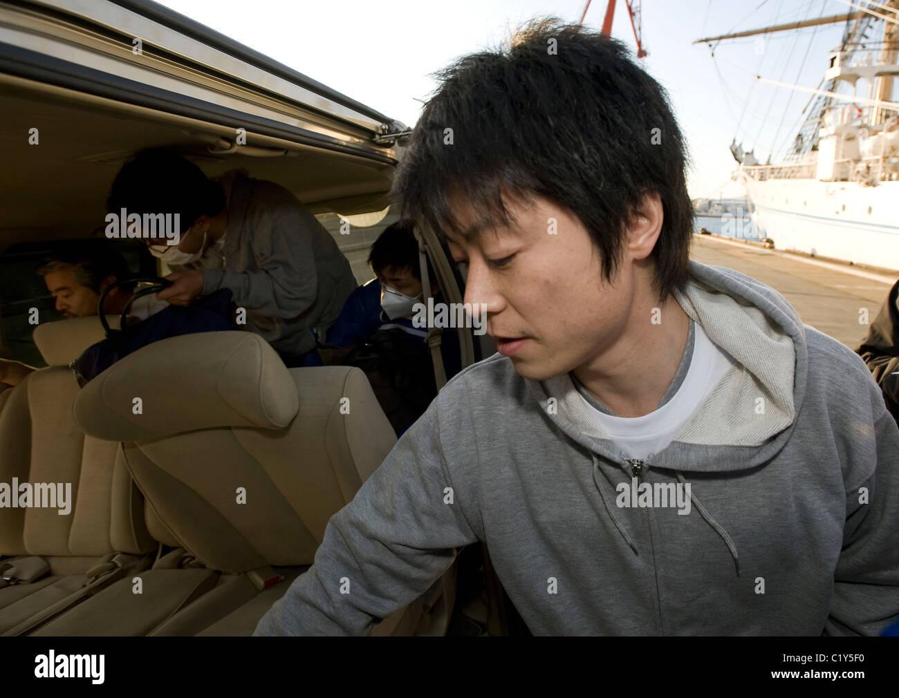 Akira Tamura, a member of the so-called Fukushima 50 alights from a vehicle prior to boarding the Kaiwomaru - Stock Image