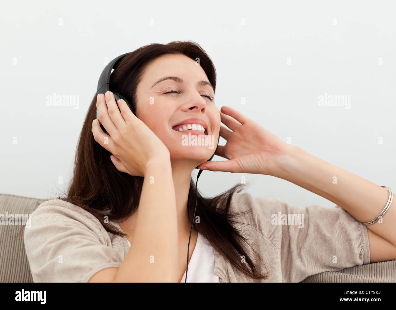 Happy woman enjoying a song on the sofa - Stock Image