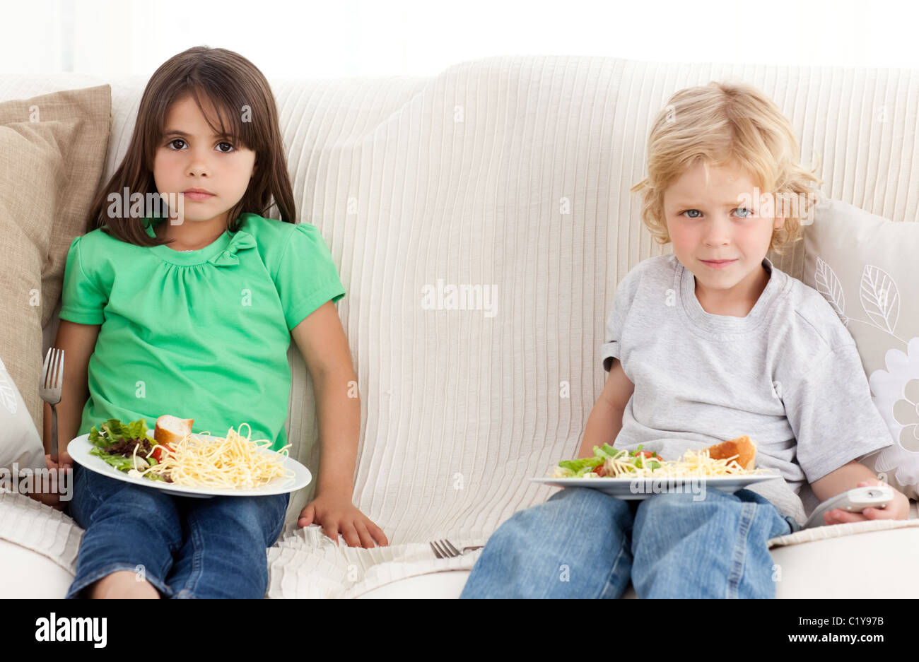 Serious brother and sister having dinner on the sofa - Stock Image
