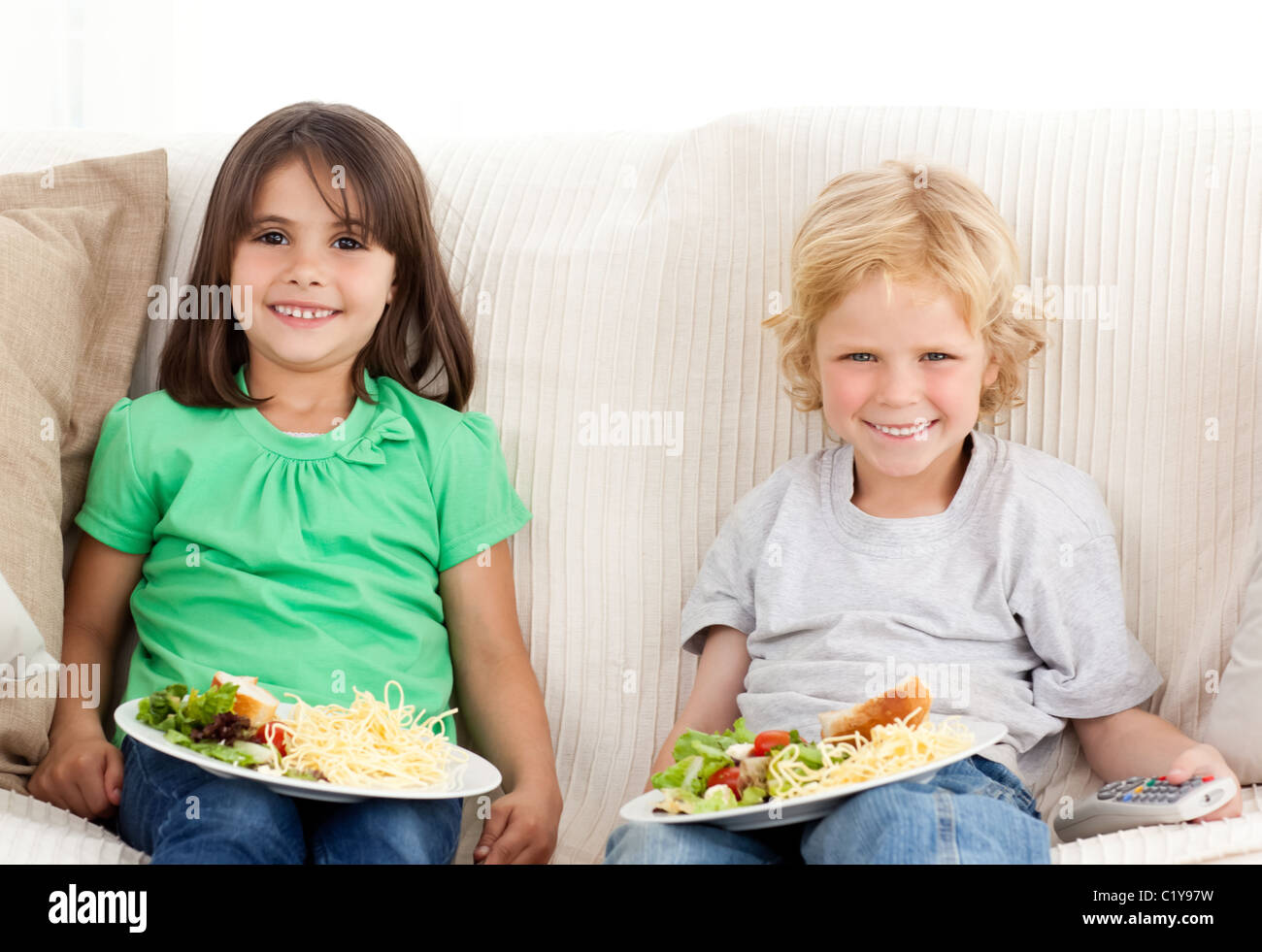 Happy brother and sister having TV dinner - Stock Image