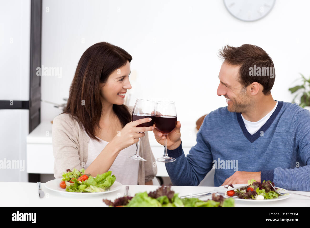 Lovely couple clinking glasses of red wine during lunch - Stock Image
