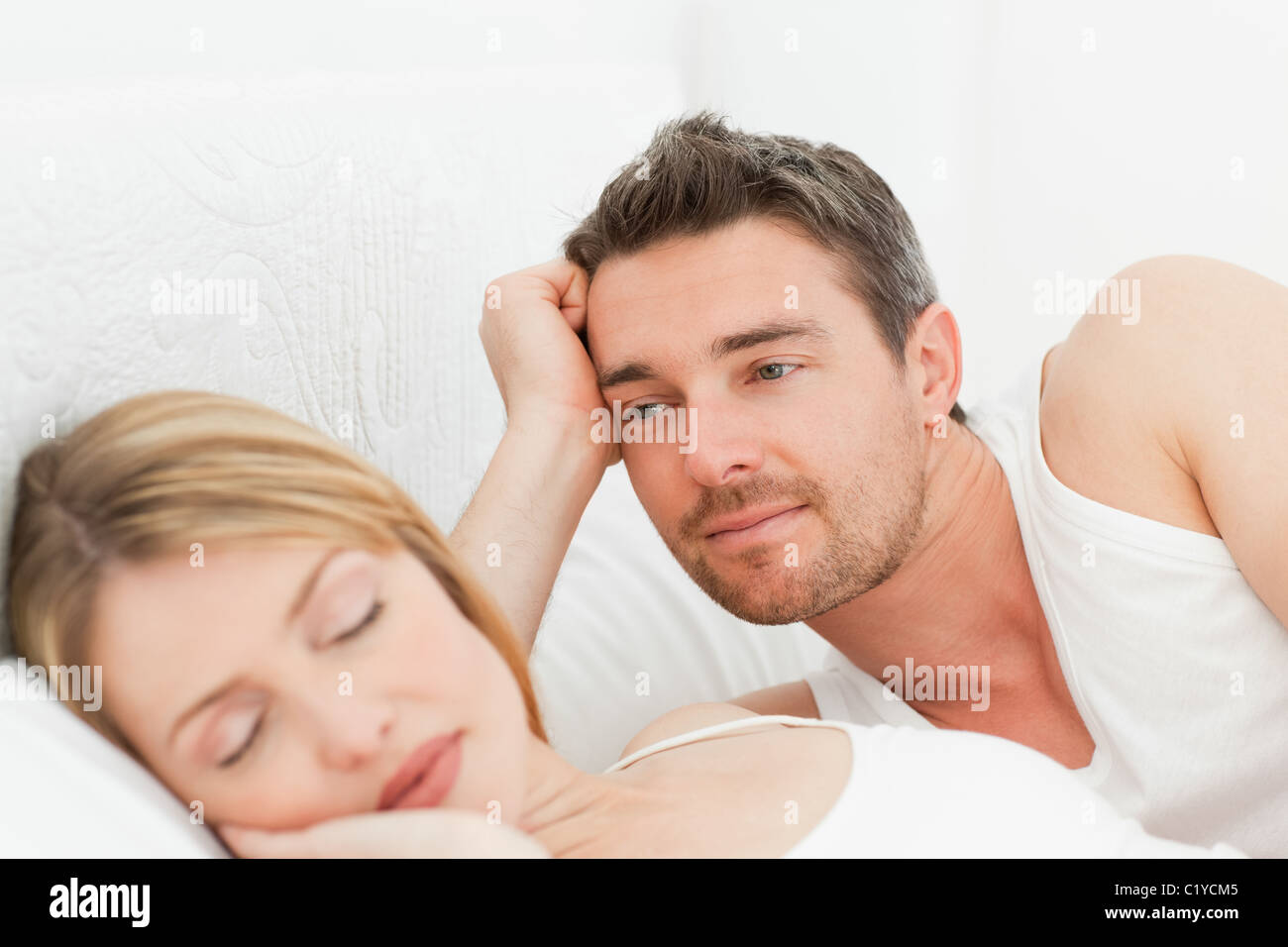 Boyfriend looking at his girlfriend who is  sleeping - Stock Image