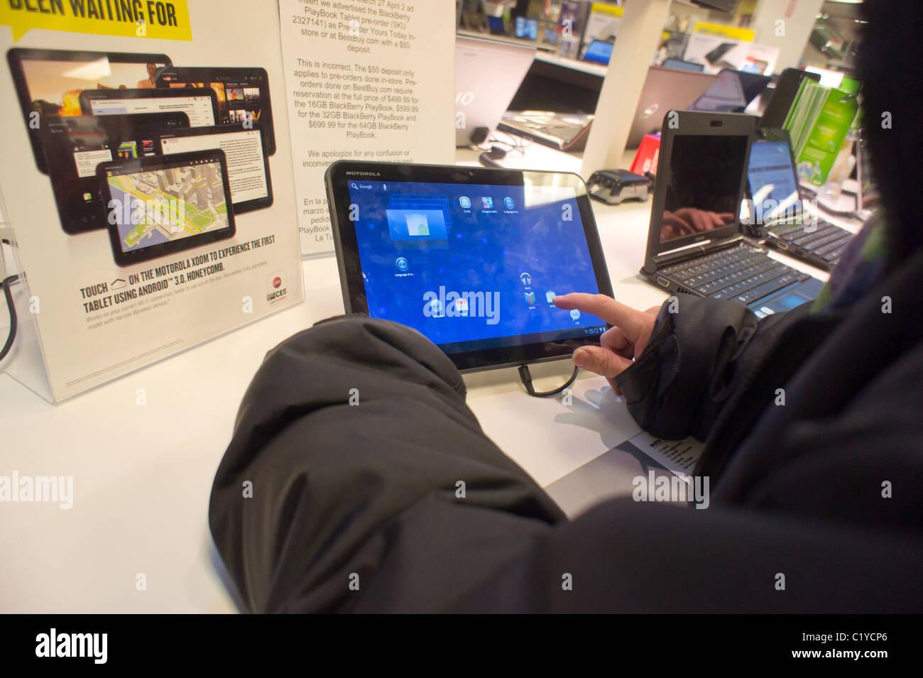 A shopper inspects a Motorola Xoom tablet computer Stock
