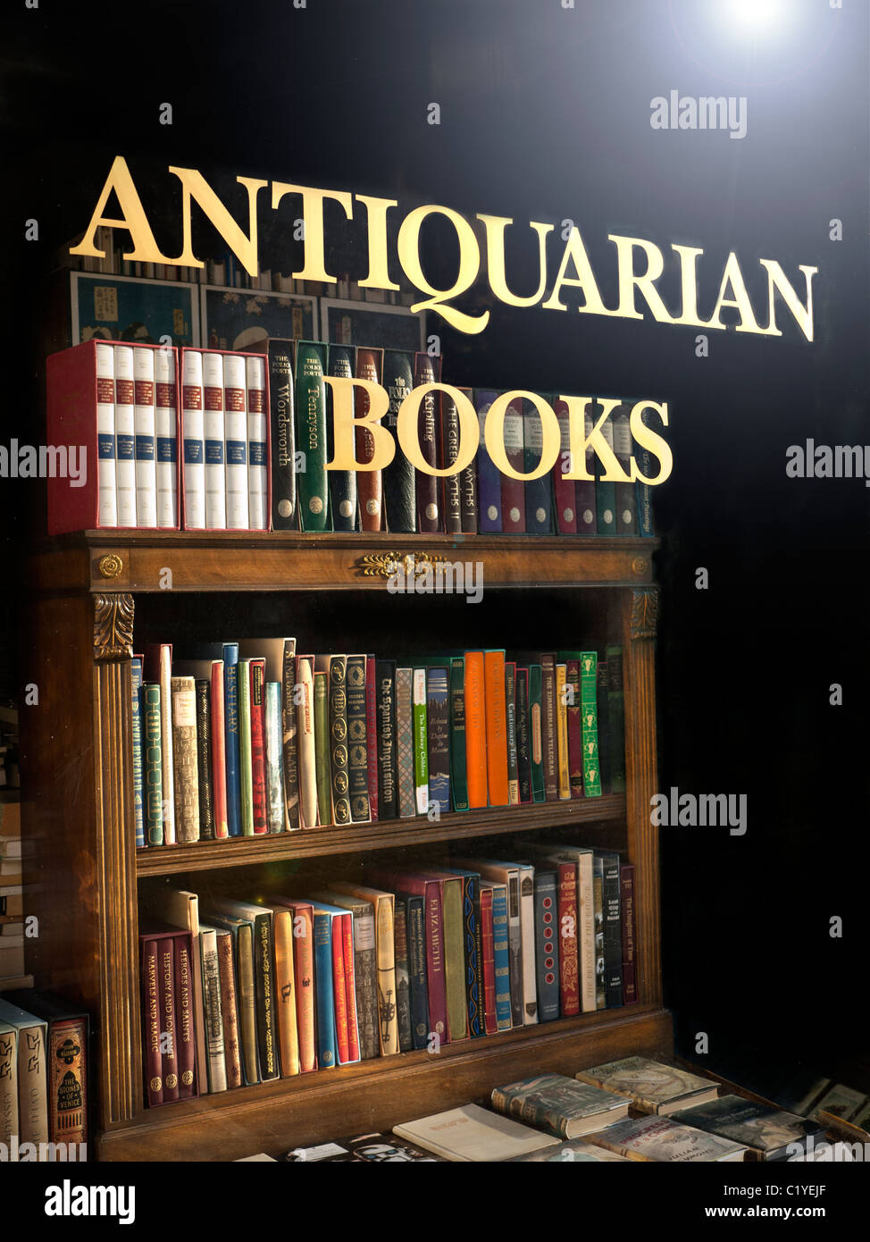 Antiquarian Bookshop window with sign and antique books and bookcase on display - Stock Image