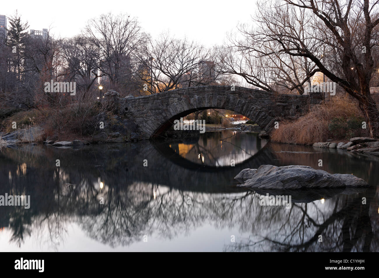 Gapstow Bridge as seen from the Pond with reflections in the water in New York's Central Park in Winter - Stock Image