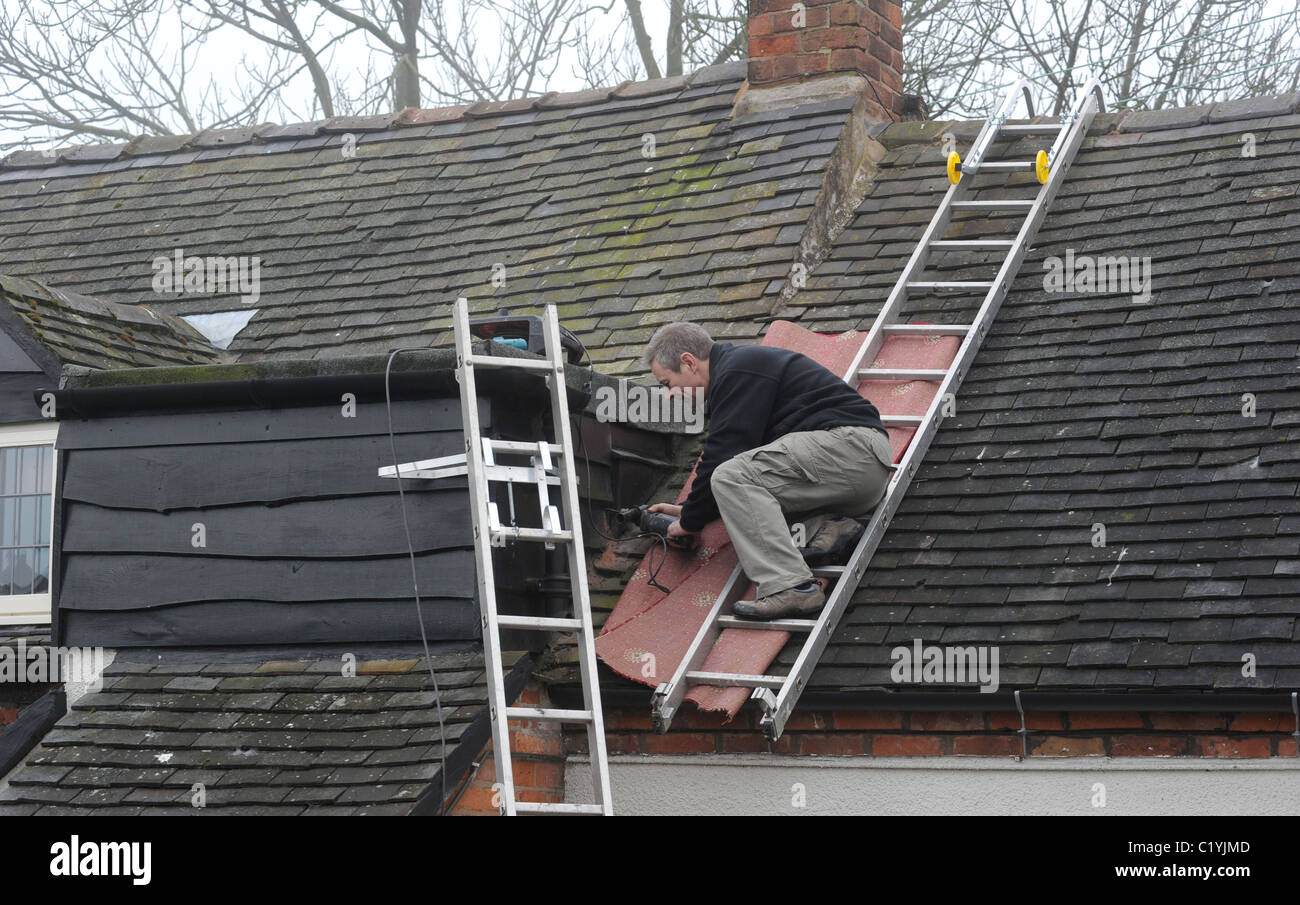 WORKMAN WORKING ON ROOF LADDERS ON DOMESTIC HOUSE RE  ROOF REPAIRS DIGITAL SWITCHOVER NEW AERIALS SIGNAL ANALOGUE - Stock Image