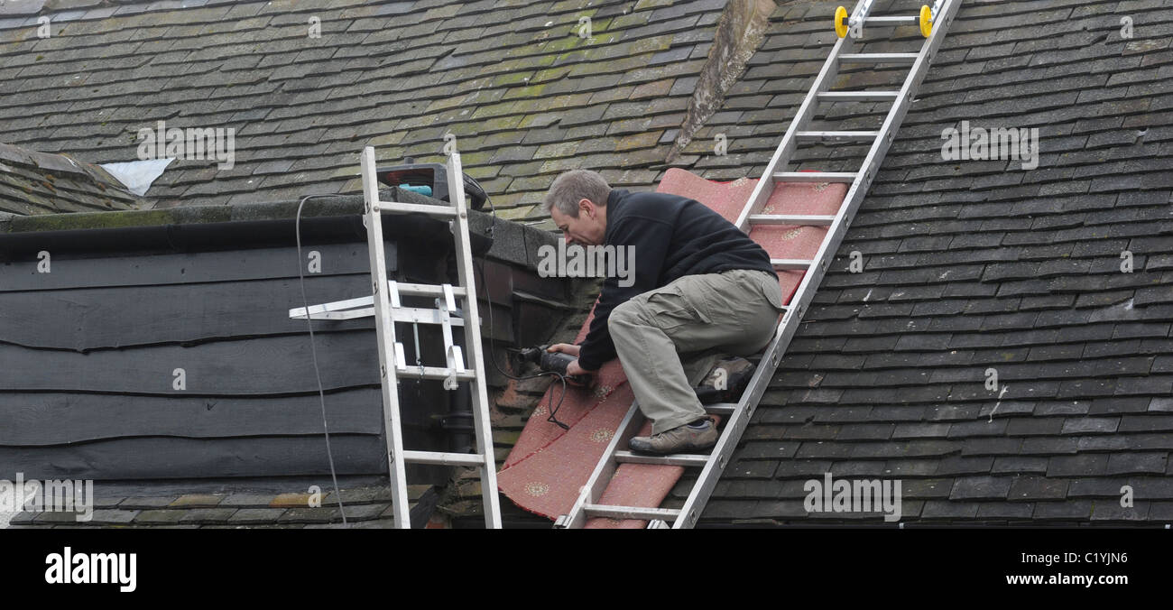 WORKMAN WORKING ON LADDERS ON DOMESTIC HOUSE RE ROOF REPAIRS DIGITAL SWITCHOVER NEW AERIALS SIGNAL ANALOGUE SWITCH - Stock Image