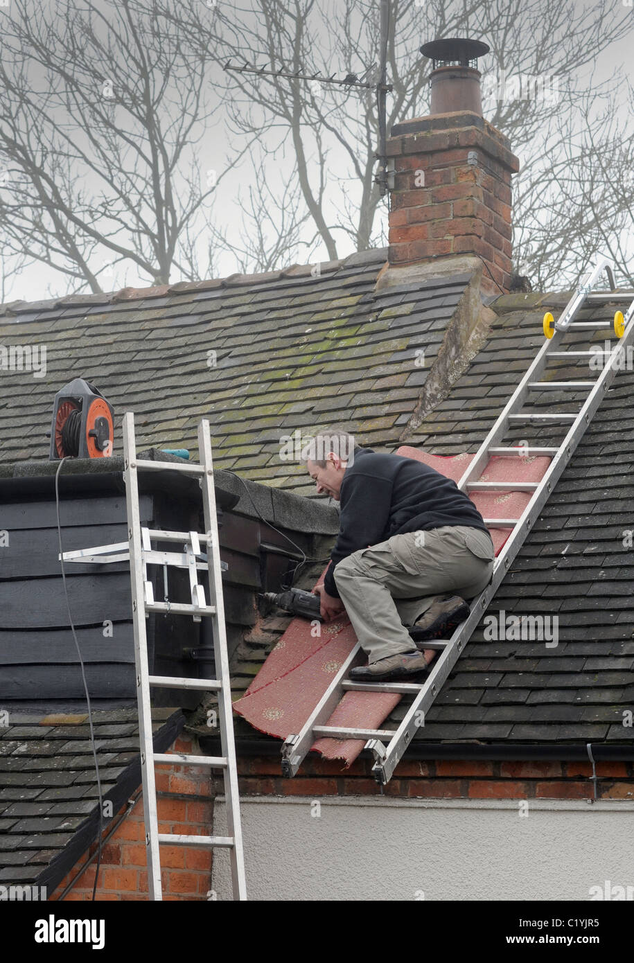 WORKMAN WORKING OFF LADDERS ON DOMESTIC HOUSE RE ROOF REPAIRS DIGITAL SWITCHOVER NEW AERIALS SIGNAL ANALOGUE SWITCH - Stock Image